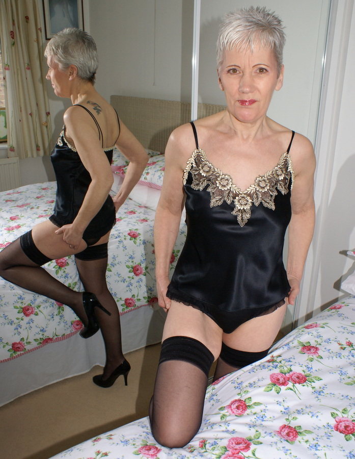 GILF in lingerie playing in the bedroom with a vibrator
