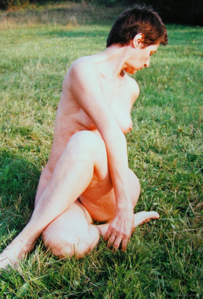 Mature slut wife sunbathing outside naked on the grass