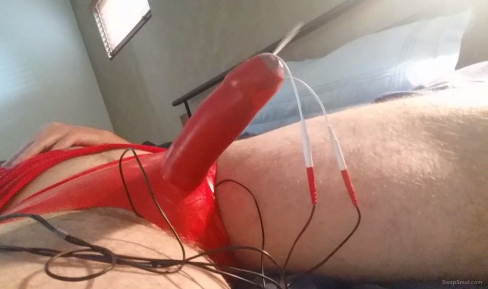 EStim fun in constrictive red latex sheath pants