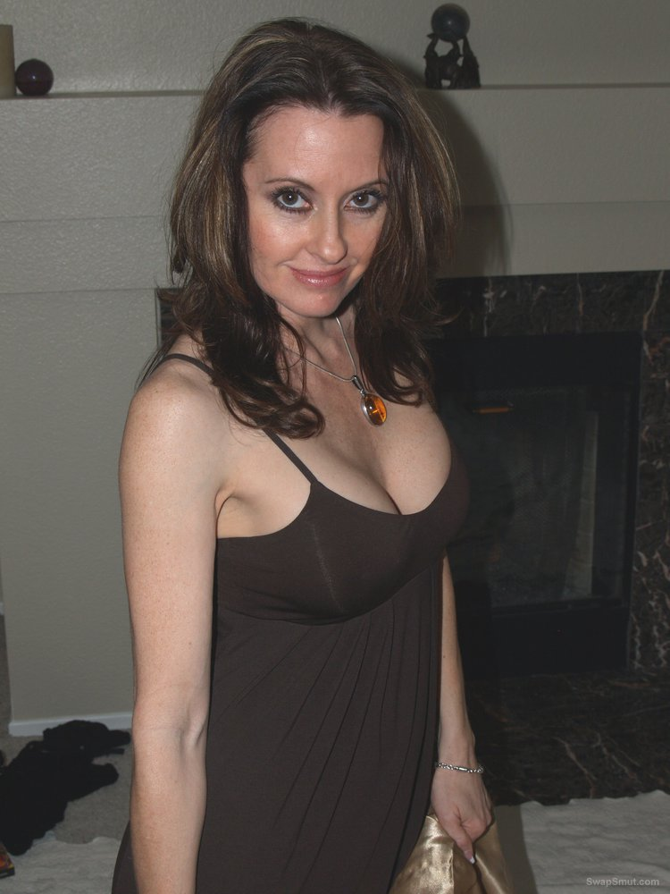 A very sexy bi milf posing at home lifting up her black dress to tease