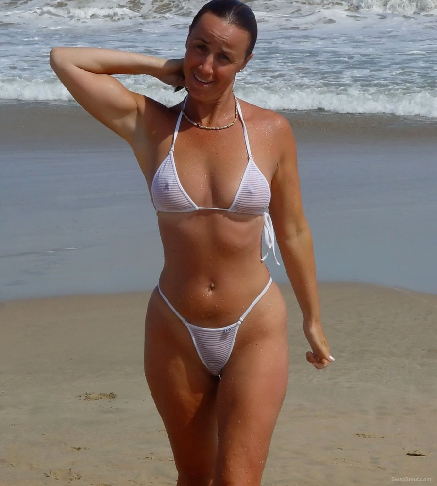 swinging milf nude on the beach and holding a big black dick