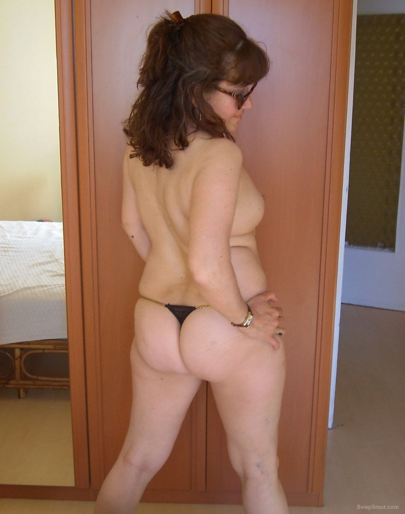 My sexy mature friend posing on my bed wearing only a thong