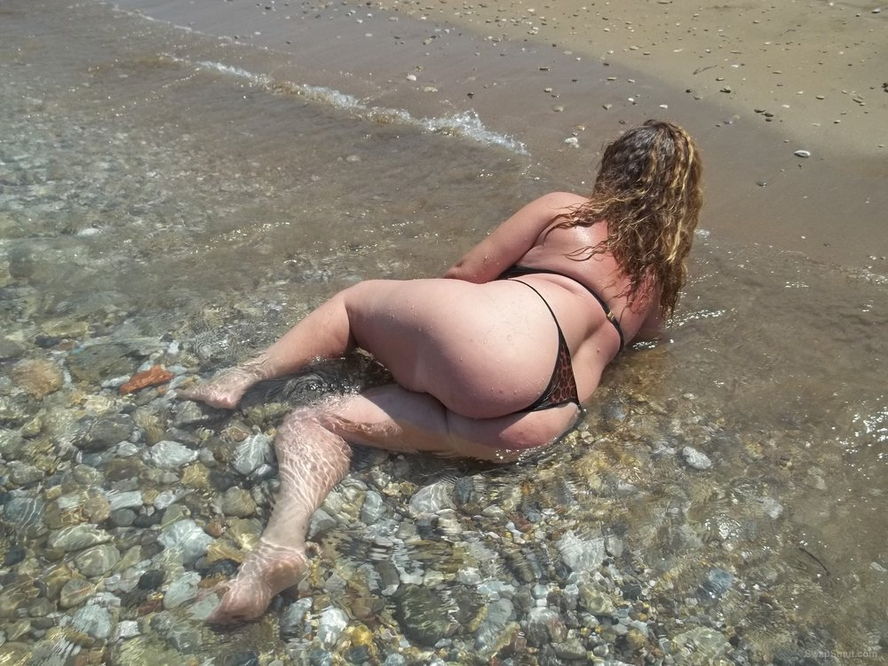 Sexy wife outdoors on beach wearing a bikini writhing in the surf