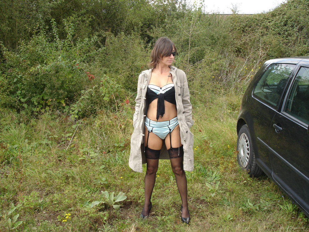 Exhibitionist wife in black and blue lingerie under long coat