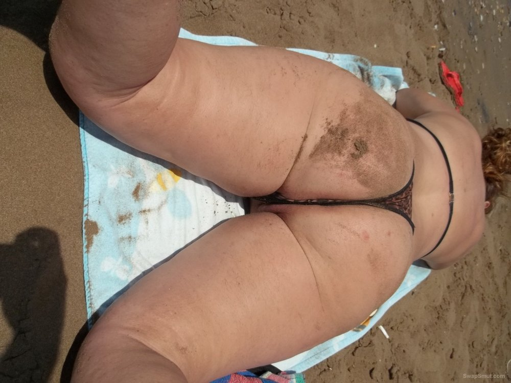 Sexy wife on beach sunbathing pulling thong to side showing pussy