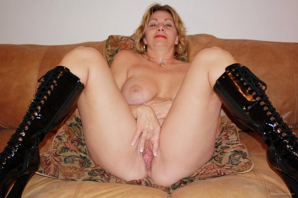 Showing off pink pussy spreading the labia lips on sofa for camera