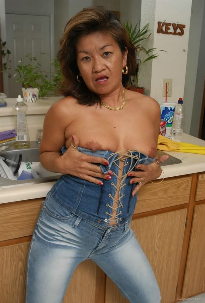 Mature Asian amateur posing for erotic pics in kitchen